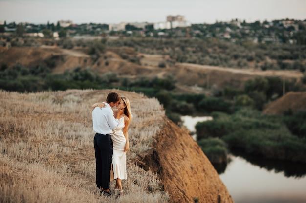 Dois amantes se abraçando no topo de uma colina com vista para a cidade e o rio.