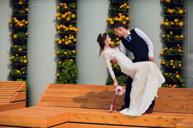 Dois amantes se sentam em um banco, os noivos agachados para descansar nos braços um do outro durante uma sessão de fotos de casamento, a noiva em um vestido branco e o noivo em um belo terno aposentado no parque.
