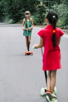 Dois, amigo feminino, ficar, ligado, scooter, olhando um ao outro