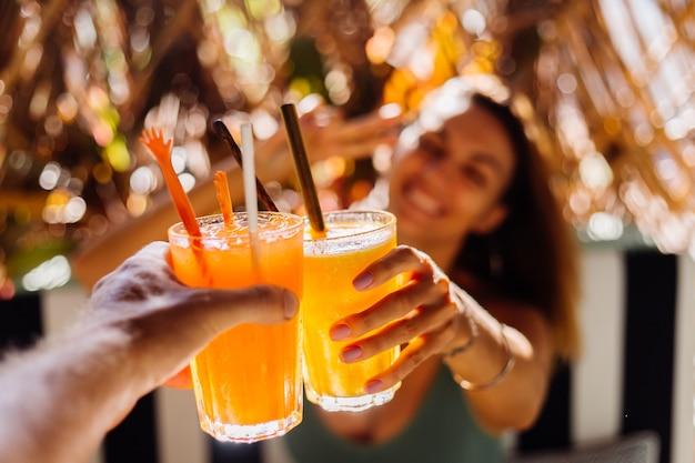 Dois amigos a tilintar em copos de saborosos cocktails tropicais num dia de sol num café