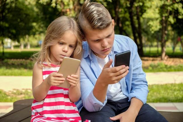 Dois amigos adolescentes felizes usando no celular enquanto relaxa no parque