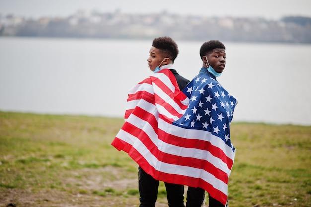 Dois amigos africanos de adolescentes com a bandeira americana no parque usando máscaras médicas protegem da quarentena do vírus de coronavírus de infecções e doenças.