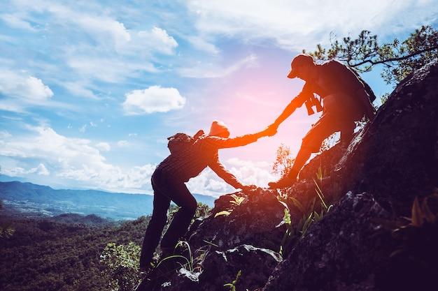Dois amigos ajudando uns aos outros e com o trabalho em equipe tentando alcançar o topo das montanhas.