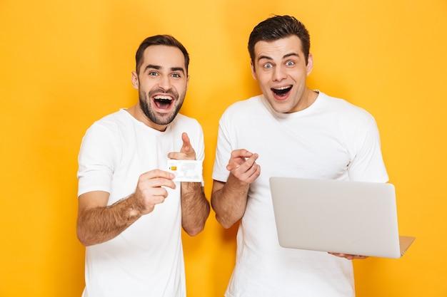 Dois amigos alegres e animados vestindo camisetas em branco, isolados na parede amarela, usando um laptop, comemorando o sucesso, mostrando um cartão de crédito de plástico