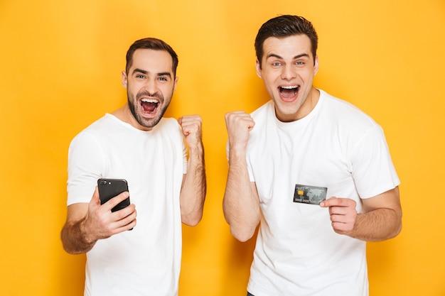 Dois amigos alegres e entusiasmados usando camisetas em branco, isolados sobre uma parede amarela, olhando para o celular, comemorando o sucesso