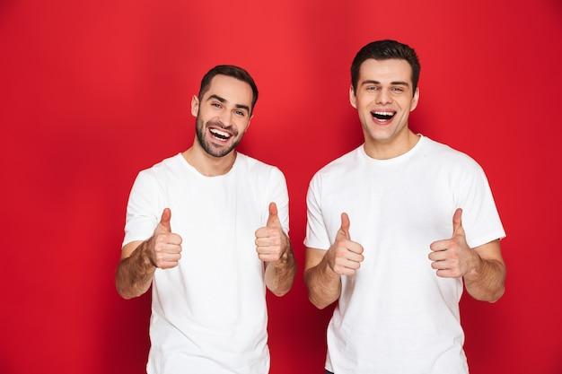 Dois amigos alegres e entusiasmados usando camisetas em branco, isolados sobre uma parede vermelha, mostrando os polegares para cima