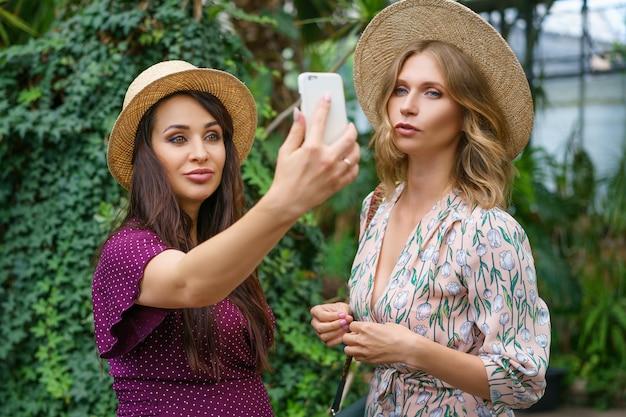 Dois amigos alegres olham para o telefone, fazem chapéus de selfie em um fundo verde natural.