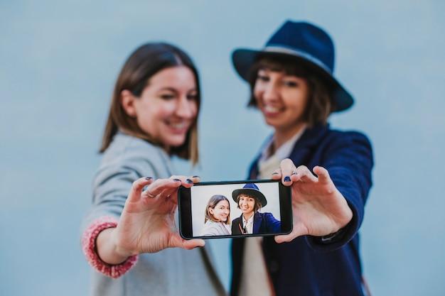 Dois amigos ao ar livre com roupas elegantes, tomando uma selfie com telefone móvel