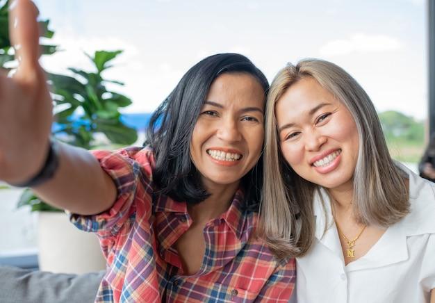 Dois amigos asiáticos tirando selfies no celular na cafeteria.