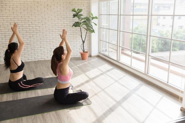 Dois amigos asiáticos treinando ioga