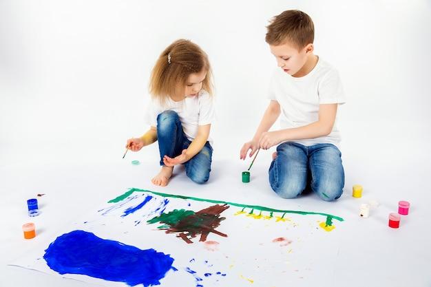 Dois amigos bonitos da criança menino e menina estão desenhando pinturas
