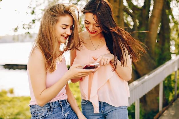 Dois amigos bonitos e brilhantes em t-shirts cor de rosa e jeans azul andando no parque de verão