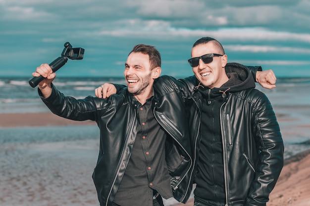 Dois amigos bonitos e sorridentes fazendo selfie usando a câmera de ação com estabilizador de cardan na praia.