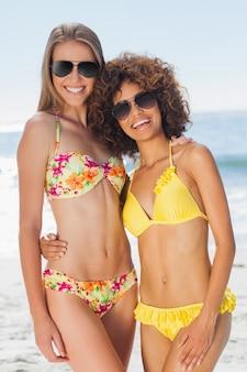 Dois amigos bonitos em biquínis usando óculos de sol posando