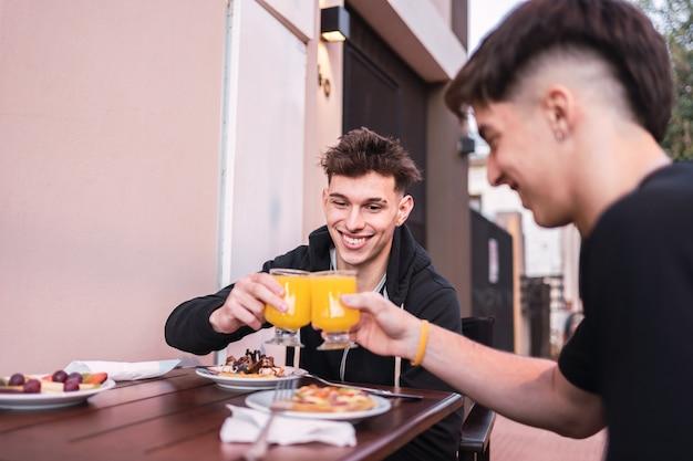 Dois amigos brindando com suco de laranja, sentados em uma mesa ao ar livre em um bar.