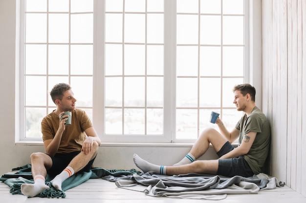 Dois amigos, café bebendo, enquanto, olhando um ao outro, sentando, perto, janela