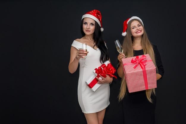 Dois amigos com caixas de presente e taças de champanhe