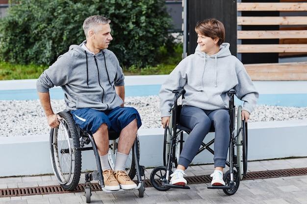 Dois amigos com deficiência sentados em cadeiras de rodas conversando um com o outro enquanto passam um tempo em ...