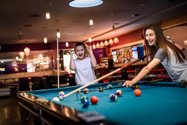 Dois amigos com dicas no bar. eles usam roupas casuais e jogam bilhar