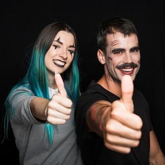 Dois amigos com maquiagem assustadora, colocando os polegares para cima