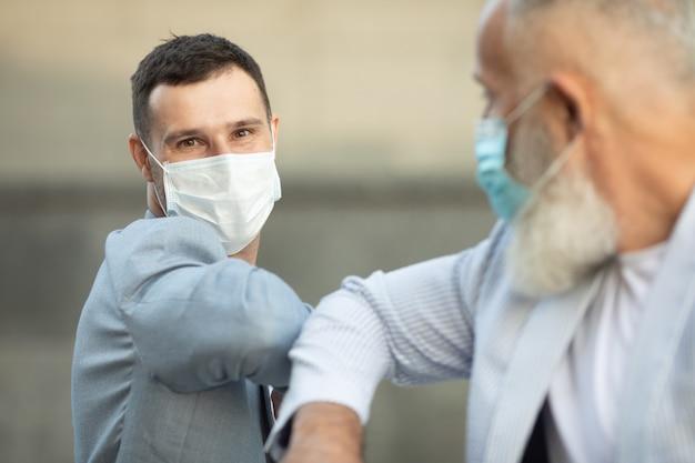 Dois amigos com máscara facial se cumprimentam com o cotovelo na rua