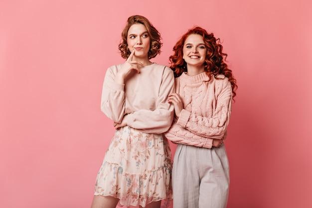 Dois amigos com roupa romântica posando juntos. vista frontal de incríveis garotas caucasianas isoladas em fundo rosa.