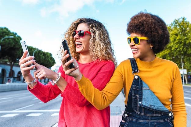 Dois amigos com smartphones na rua, conceito de tecnologia e comunicação