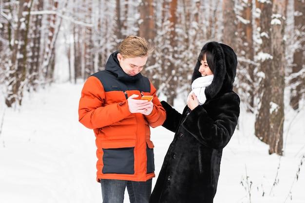 Dois amigos com um smartphone na natureza de inverno.