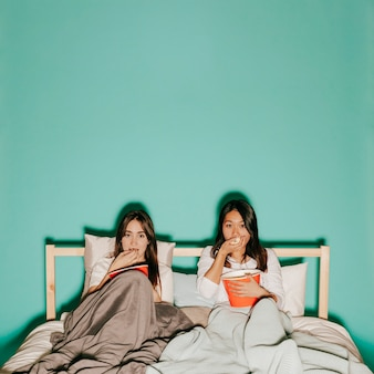 Dois amigos comendo pipoca durante um filme interessante