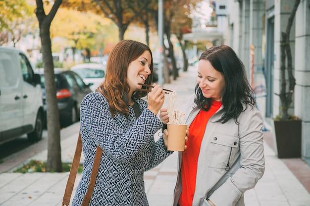 Dois amigos compartilhando alguns nuddles na rua