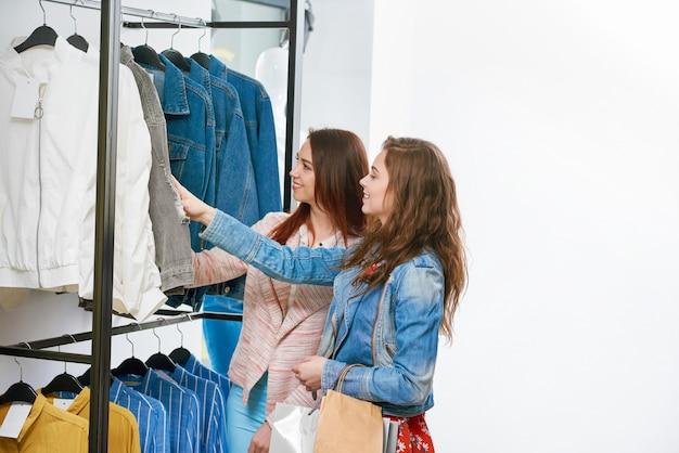 Dois amigos comprando roupas na loja.