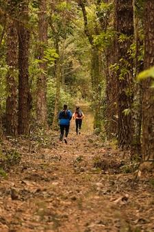 Dois amigos correndo intensamente no caminho da selva ao pôr do sol