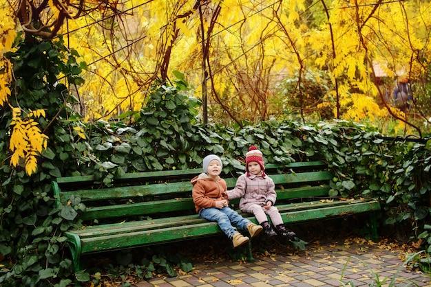 Dois amigos crianças felizes sorridentes, menino e menina sentados no banco