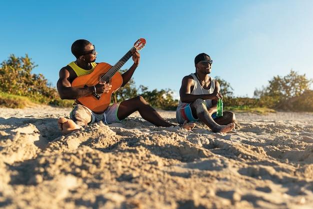 Dois amigos cubanos se divertindo na praia com seu violão. conceito de amizade.