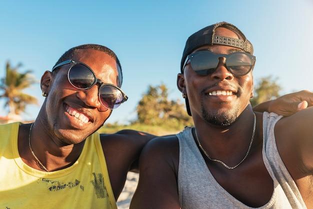 Dois amigos cubanos tirando uma selfie com seu celular. conceito de amizade.
