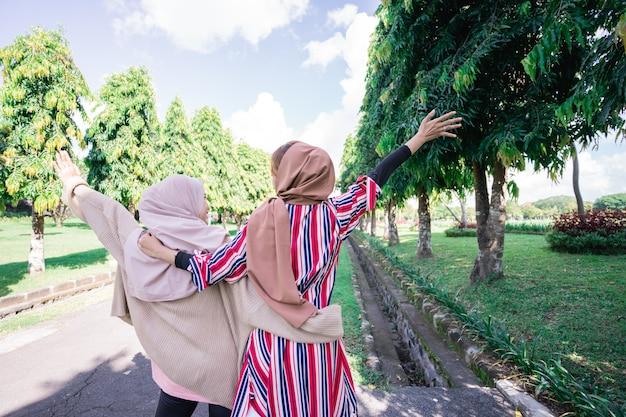 Dois amigos curtindo o sol de verão e andando de mãos dadas no parque fotografam de costas