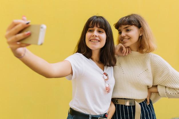 Dois amigos de escola elegante garota brincando faz selfie e sorrindo sobre o fundo amarelo.