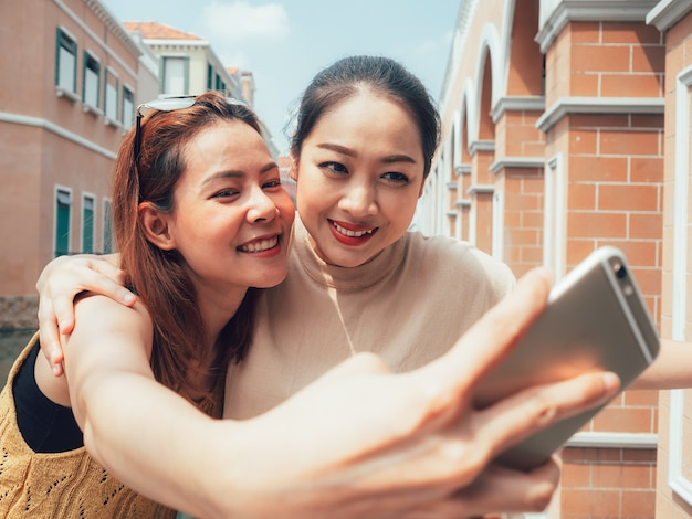 Dois amigos de garotas turísticas estão tomando selfie com a vista da cidade.