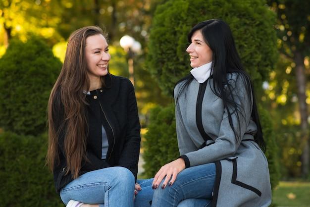 Dois amigos de meninas morena caucasianos, conversando enquanto está sentado no parque ensolarado de outono.