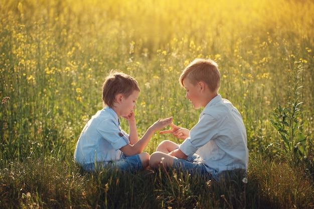 Dois amigos de meninos pequenos que jogam - pedra, tesouras, jogo de papel no dia de verão.