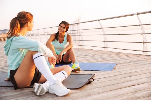 Dois amigos de mulheres esportes ao ar livre na praia sentado conversando uns com os outros Foto Premium