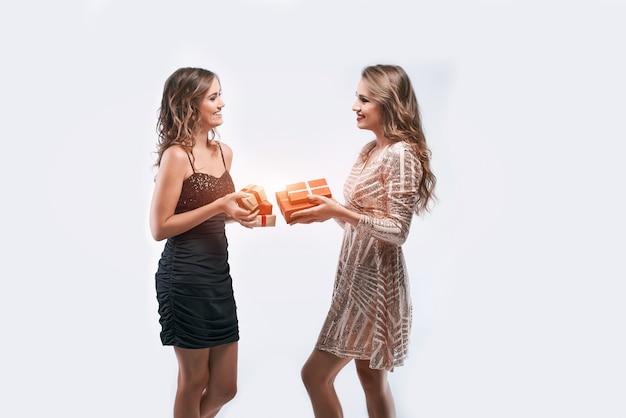 Dois amigos de mulheres felizes trocando presentes isolados no branco