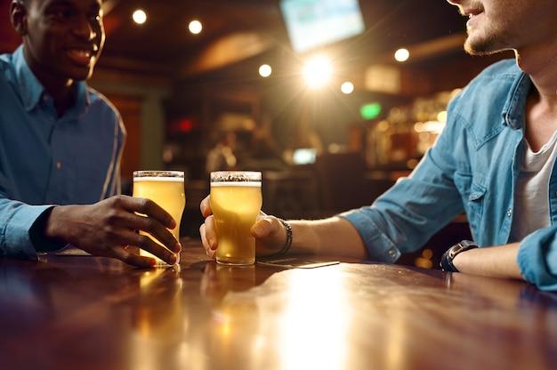 Dois amigos do sexo masculino bebem cerveja fresca no bar. pessoas relaxam em um bar, estilo de vida noturno, amizade, celebração de evento, lazer masculino em restaurante