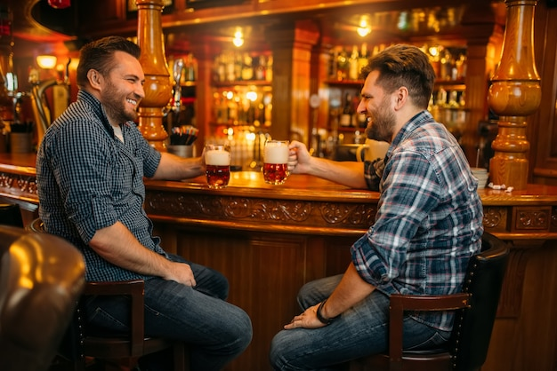 Dois amigos do sexo masculino bebem cerveja no balcão de um bar