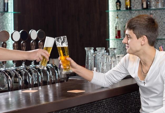 Dois amigos do sexo masculino brindando enquanto bebem um copo de cerveja juntos, sentados no balcão