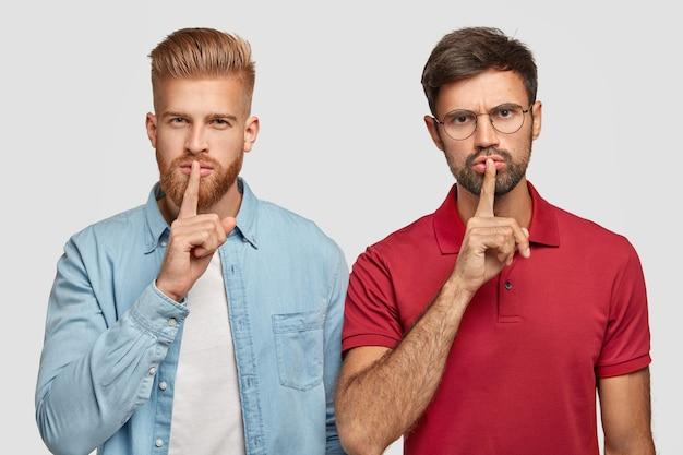 Dois amigos do sexo masculino com barbas grossas, mantêm os dedos da frente nos lábios, olham secretamente, contam informações muito particulares, ficam um ao lado do outro, isolados sobre uma parede branca. pessoas, conceito secreto
