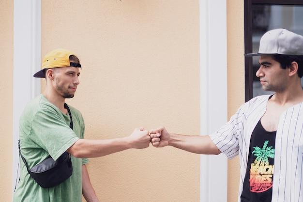 Dois amigos do sexo masculino cooperam e batem os punhos um no outro, trabalho em equipe e conceito de amizade
