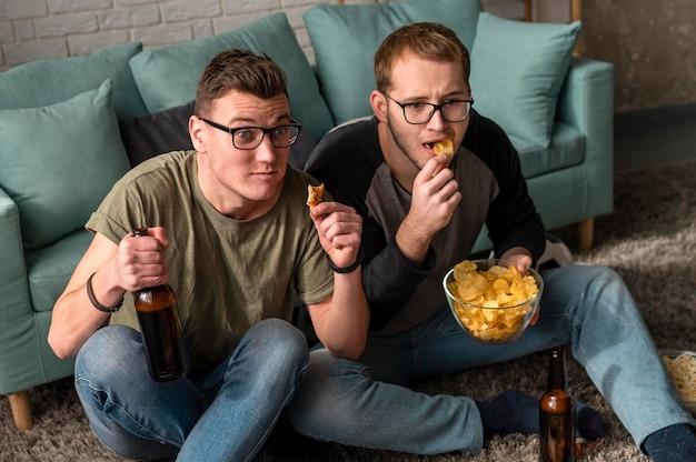 Dois amigos do sexo masculino tomando cerveja com lanches e assistindo esportes na tv