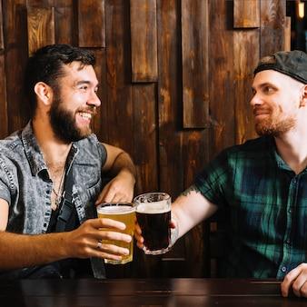 Dois amigos do sexo masculino torcendo com copos de bebidas alcoólicas