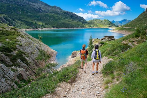 Dois amigos durante uma caminhada nas montanhas andando perto de um alpin
